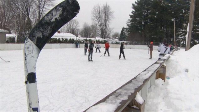 Des gens jouent au hockey sur une patinoire extérieure.