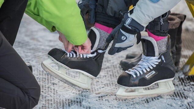Une personne en aide une autre à chausser ses patins.