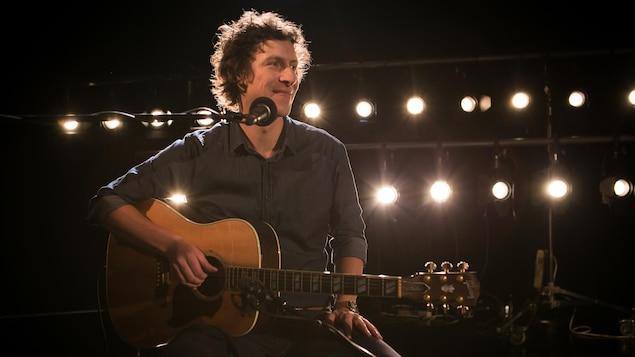 Patrice Michaud assis sur un siège sur scène, avec sa guitare.