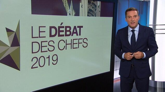 Patrice Roy à côté d'un écran où l'on peut lire « Le débat des chefs 2019 ».