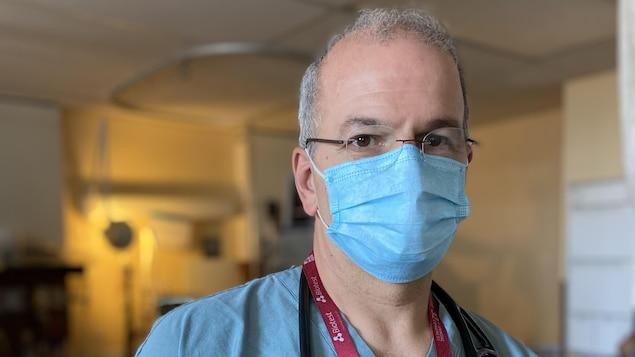 Le docteur Bellemare porte un sarrau bleu, un masque et a un stéthoscope autour du cou.
