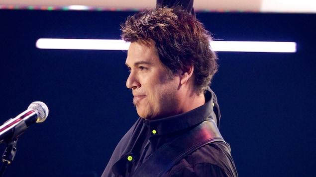Le chanteur Patrick Bourgeois, cheveux courts, guitare à la main en performance à l'émission «C'est ma toune» en 2014. Un micro se tient devant lui.