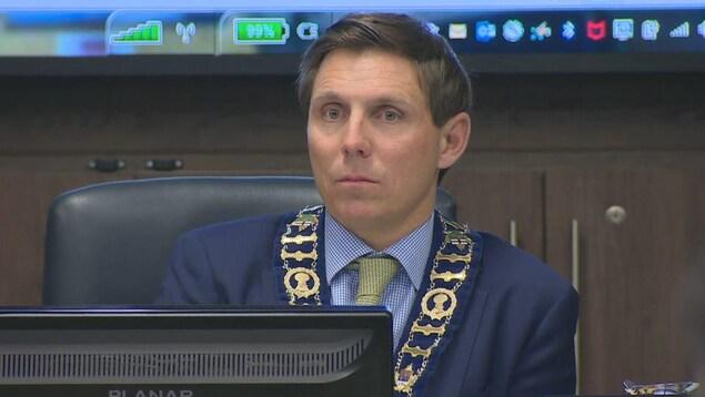Un homme en complet bleu regarde devant lui, assis derrière un écran d'ordinateur.