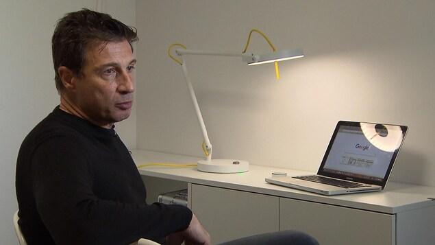 M. Burle est assis devant un bureau sur lequel se trouvent la lampe li-fi et un ordinateur.
