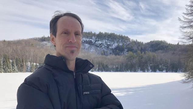 Patrick Gravel, de la Coopérative de solidarité des forêts et des gens, devant un lac gelé.