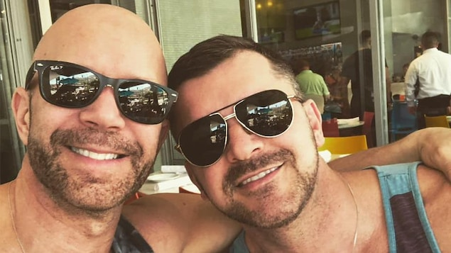 Deux hommes souriants assis sur une terrasse. Ils sont en camisoles et portent des lunettes fumées.