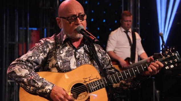 Patrick Norman chante et joue de la guitare.