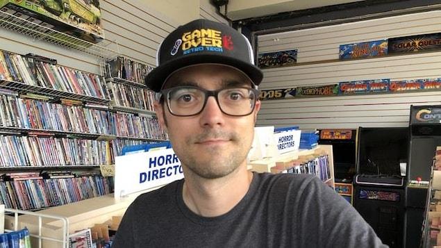 Patrick Parisé dans son magasin, devant des étagères remplies de films.