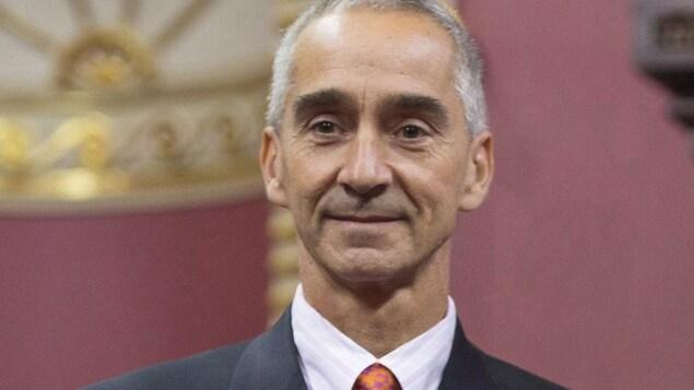 Patrick Pichette sourit et porte l'insigne de l'Ordre national du Québec sur son veston.