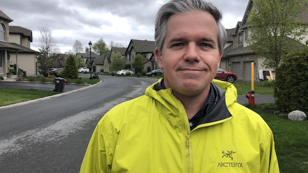 Un homme se laisse prendre en photo à l'extérieur, dans un quartier résidentiel.