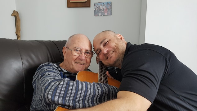 Earl Leblanc et Patrick Truner se font une accolade autour d'une guitare.