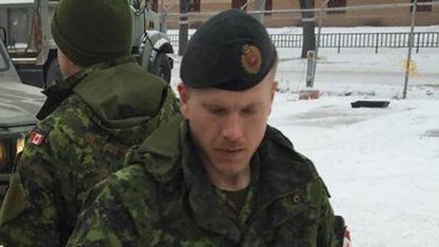 Un homme vu en gros plan. Il est revêtu de l'uniforme de l'armée. La photo a été prise à l'extérieur, en hiver. L'arrière-plan montre d'autres soldats et des véhicules de l'armée.