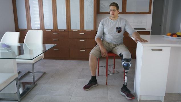 Portrait de Paul-André Perreault avec sa prothèse dans sa cuisine.