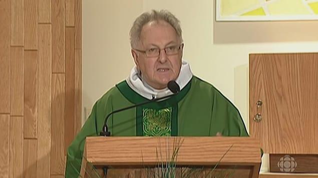 Paul Breau, vêtu d'une soutane verte, lit une messe.