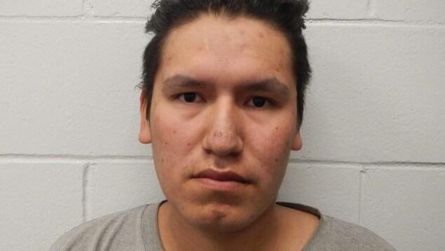 Un jeune homme accusé par la police de multiples infractions sexuelles pose devant un mur.