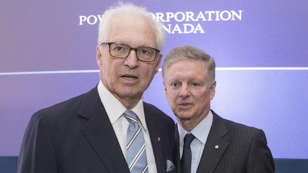 Plan moyen des deux hommes devant le logo de Power.