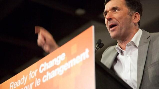 Un homme s'exprimant sur un podium orange
