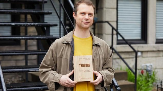 L'homme est debout à l'extérieur devant un escalier et il tient son livre dans ses mains.