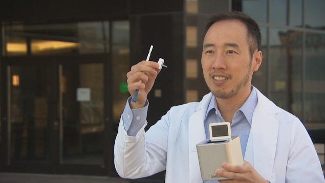 Un homme avec un sarrau tient une trousse de dépistage dans ses mains.
