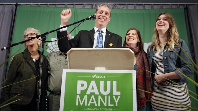 Accompagné de membres de sa famille, Paul Manly s'adresse au micro, le sourire aux lèvres et le poing levé en signe de victoire.