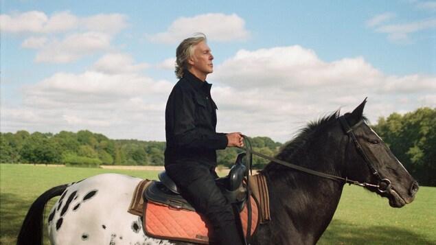 Un homme à cheval vu de profil.