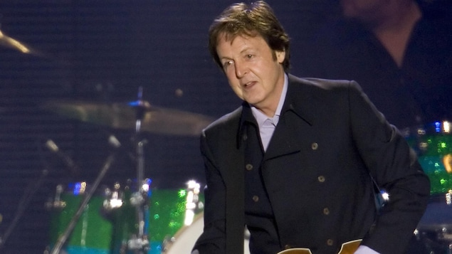 Paul McCartney sourit tout en jouant de la guitare lors d'un concert.