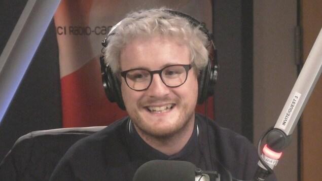 Dans un studio de Radio-Canada, un jeune homme blond avec des lunettes noires sourit en regardant en biais. Il a un casque sur les oreilles et un micro devant la bouche.