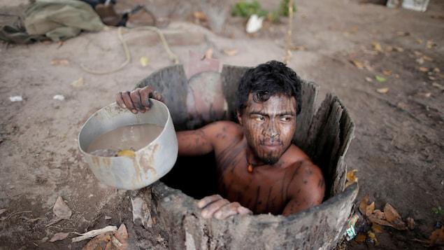Un homme couvert de maquillage noir sort d'un puits.