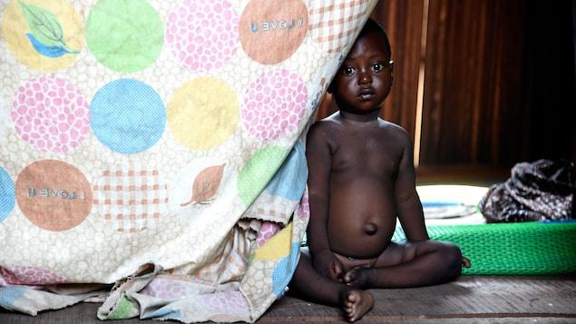 Un enfant assis sur le sol.
