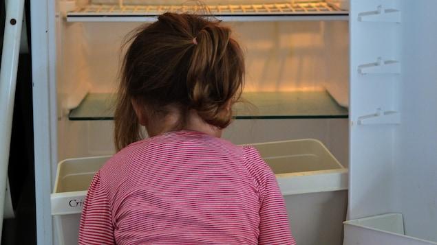 Une fillette assise devant un réfrigérateur vide.