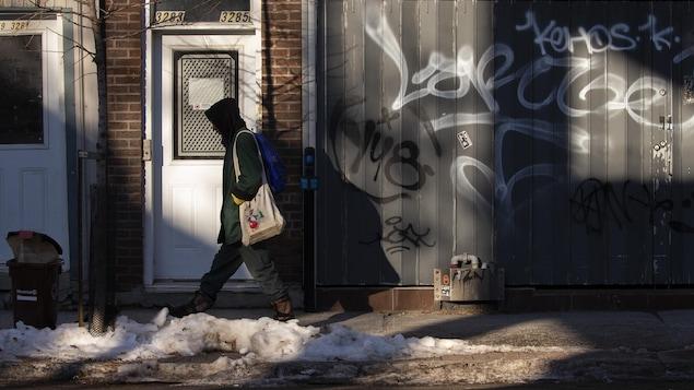 Un homme, vu de profil, marche sur le trottoir d'un quartier populaire. On voit des graffitis sur les murs des bâtiments.