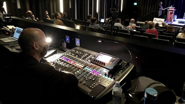 Dans la salle de spectacle. Un homme est assis devant une console de son. En arrière-plan on aperçoit des spectateurs assis et une personne sur la scène.