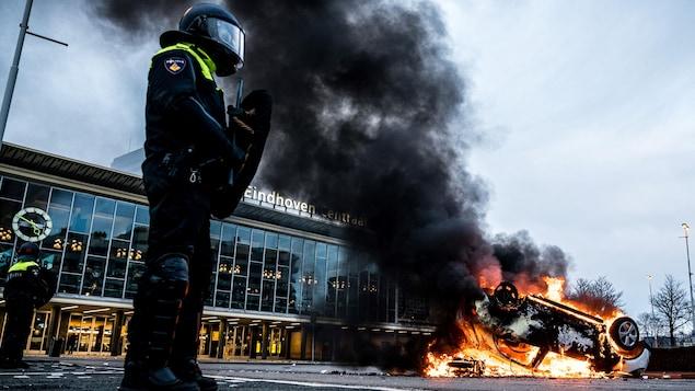 Une voiture brûle devant la gare à Eindhoven.