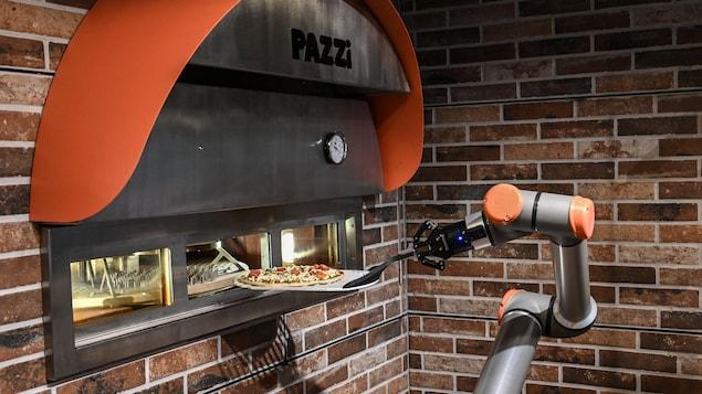 Le bras articulé d'un robot porte une pizza sur une plaque qu'il s'apprête à déposer dans un four.
