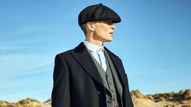 Un homme porte une casquette et tient une arme à la main droite.