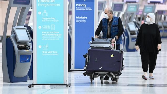 Deux voyageurs près d'un kiosque d'enregistrement de bagages à l'aéroport Pearson.