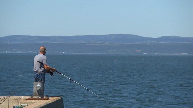 Homme pêchant le bar rayé sur le quai de Gaspé.