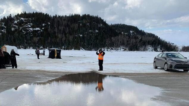 Un homme marche sur la glace devant une flaque d'eau.