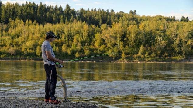 Un homme avec une canne à pêche près d'une rivière.