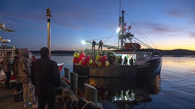 Des gens sur le quai observent un bateau de pêche sur le point de prendre la mer.