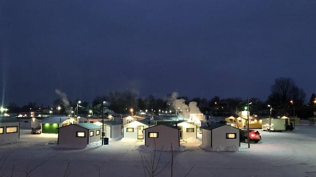 Des petites cabanes de pêcheurs blanches et vertes, avec de la fumée qui sort des cheminées, très tôt le matin