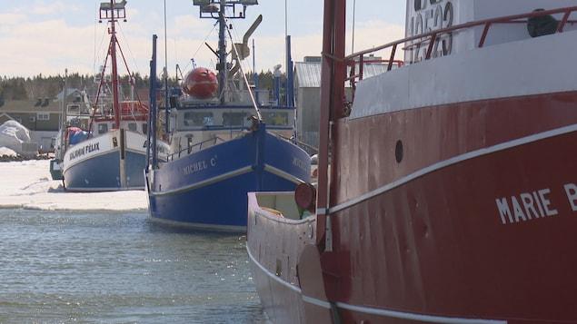 Trois bateaux sont amarrés au quai de Caraquet.