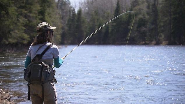 Une femme pêche sur le bord d'une rivière.
