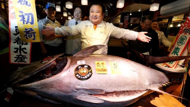 Un homme pose devant un thon de 212 kg. dans un restaurant à sushis de Tokyo.