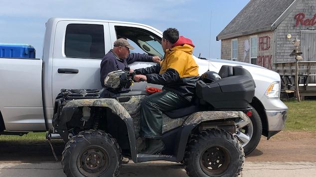 Un homme assis sur un véhicule tout-terrain discute avec un autre homme près de la mer.