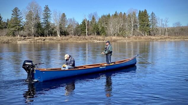 Des pêcheurs se trouvent à bord d'un petit bateau à moteur.