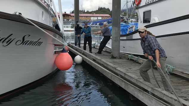 On peut voir des pêcheurs de Valdez à quai tirer sur les amarres de leur bateau.