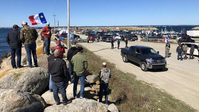 Groupe de pêcheurs, certains tenant des drapeaux acadiens, près d'un quai.