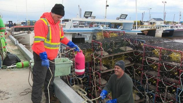 Des pêcheurs de homard préparent leur bateau à Pigeon Hill, dans la Péninsule acadienne.