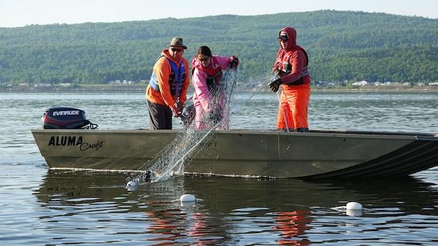 Trois pêcheurs relevent un filet de pêche debout dans leur bateau.